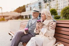 Deux retraités s'asseyent sur un banc avec un verre de café dans leurs mains Ils reposent l'embrassement et le sourire Photo stock
