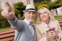 Deux retraités s'asseyent sur un banc avec un verre de café dans leurs mains L'homme montre à la femme quelque chose en avant Images libres de droits