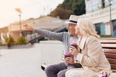 Deux retraités s'asseyent sur un banc avec un verre de café dans leurs mains L'homme montre à la femme quelque chose en avant Photo stock