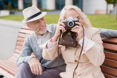 Deux retraités s'asseyent sur un banc et prennent des photos sur un vieil appareil-photo de film Ils sourient Image stock