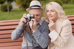Deux retraités s'asseyent sur un banc et prennent des photos sur un vieil appareil-photo de film Ils sourient Photographie stock libre de droits