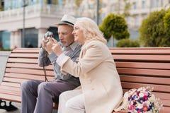 Deux retraités s'asseyent sur un banc et prennent des photos sur un vieil appareil-photo de film Ils sourient Photo libre de droits