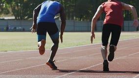 Deux rivaux commençant à courir de se tapissent début, désir de gagner, concurrence banque de vidéos