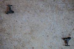 Deux robinets se sont étendus à plat sur le béton Photo libre de droits