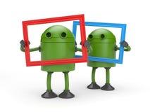 Deux robots verts avec le cadre de tableau Photographie stock