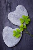 Deux roches en forme de coeur grises avec des trèfles sur un backgro de tuile Images stock