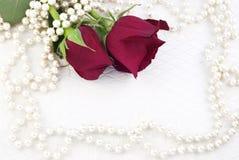 Deux roses et perles rouges Photographie stock