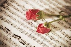 Deux roses roses sur des feuilles de notes musicales Photographie stock libre de droits