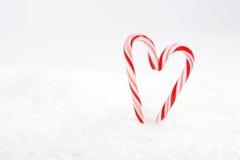 Deux rouges et cannes de sucrerie blanches au coeur forment sur la neige Photographie stock libre de droits