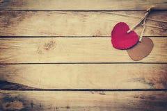 Deux rouges et coeur brun sur le fond en bois Images stock