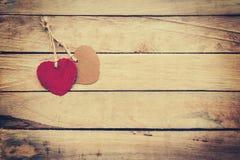 Deux rouges et coeur brun sur le fond en bois Photos stock