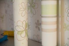 Deux rouleaux de papier peint se tiennent contre le mur avec le papier peint floral Photos stock