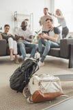deux sacs à dos et longboard sur le premier plan et le groupe d'amis multi-ethniques avec le jeu de manettes photos stock