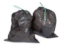 Deux sacs d'ordures attachés sur le blanc images stock