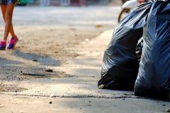 Deux sacs de déchets sur le rez-de-chaussée de rue avec un fond femelle t de jambes photo stock