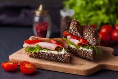 Deux sandwichs avec de la salade, les tomates fraîches et le jambon sur le verrat en bois photos libres de droits