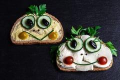 Deux sandwichs drôles sur le plateau d'ardoise photographie stock libre de droits