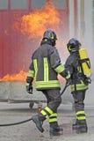 DEUX sapeurs-pompiers avec des bouteilles d'oxygène outre du feu photo libre de droits