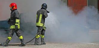 Deux sapeurs-pompiers avec l'uniforme et le casque de protection pendant un sapin photo libre de droits