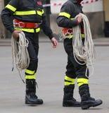 Deux sapeurs-pompiers avec une corde pendant l'opération de sauvetage photo libre de droits