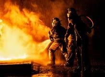 Deux sapeurs-pompiers combattant le feu avec de l'eau un tuyau et photo libre de droits