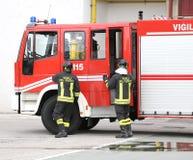 deux sapeurs-pompiers d'Italiens descendent des camions de pompiers photos stock