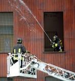 Deux sapeurs-pompiers dans l'action photographie stock libre de droits