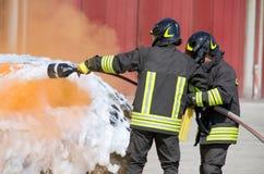 Deux sapeurs-pompiers dans l'action avec la mousse Image libre de droits