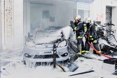 Deux sapeurs-pompiers dans l'intervention sur la voiture brûlée image libre de droits