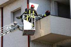 Deux sapeurs-pompiers dans la cage élevée de la pompe à incendie photos libres de droits