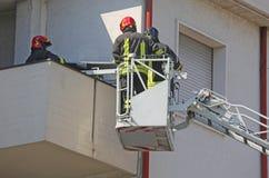 Deux sapeurs-pompiers dans la cage de la pompe à incendie photographie stock libre de droits