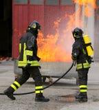 Deux sapeurs-pompiers intrépides pendant l'exercice avec un réservoir plein o photos libres de droits