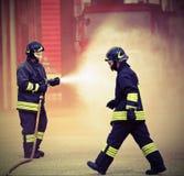 Deux sapeurs-pompiers pendant s'éteindre d'un feu utilisant les FO images libres de droits