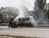 Deux sapeurs-pompiers s'éteignent une voiture brûlante du côté de la route Ville d'Istra, région de Moscou images stock