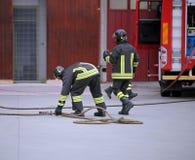 Deux sapeurs-pompiers tirant dans l'action photo stock