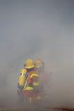 Deux sapeurs-pompiers travaille la bordure avec de la fumée Images stock