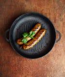 Deux saucisses faites maison avec le persil dans une poêle sur un fond en bois Photos stock