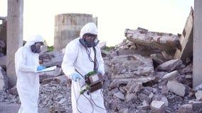 Deux scientifiques dans les tenues de protection et les masques et un dosimètre personnel de rayonnements ionisants, marchent le  clips vidéos