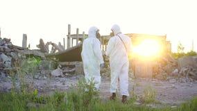 Deux scientifiques dans les tenues de protection et les masques et un surveillant de rayonnement, marchent le rayonnement de mesu banque de vidéos