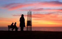 Deux sculptures deux spectateurs, sculpture en lever de soleil par la mer Photo stock