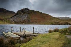 Deux se sont dégradés des bateaux amarrés à la jetée sur Llyn Dywarchen en parc national de Snowdonia images libres de droits