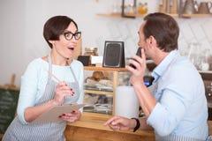Deux serveurs dans les tabliers communiquant en café Photographie stock libre de droits