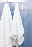 Deux serviettes blanches accrochant sur des portes de douche Photo libre de droits