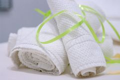 Deux serviettes blanches roulées et attachées avec le lien vert sur la table de massage photographie stock