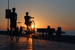 Deux silhouettes de cyclistes sur le remblai de plage de mer images libres de droits