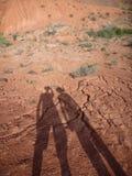 Deux silhouettes de voyageurs au sol sec Photos stock