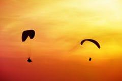 Deux silhouettes des parachutistes sont vole sur le coucher du soleil de fond Image libre de droits