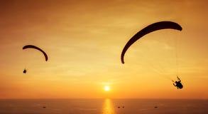 Deux silhouettes des parachutistes sont vole sur le coucher du soleil de fond Photos libres de droits