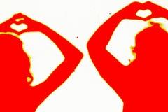 Deux silhouettes des personnes en rouge faisant un amour signent image libre de droits