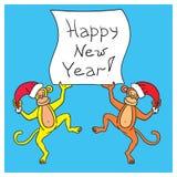 Deux singes tenant une affiche avec voix pour heureux de félicitation un nouveau Photographie stock libre de droits